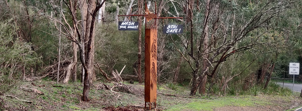 A metal totem at the entrance to Bend of Islands with COVID-related messages hanging from it.